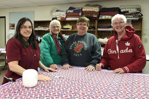 "Quilting volunteers Pam Toney, left, April Davis, Sherry Fick, and Susie Engelman, gather together in their ""quilting classroom"" at Grace Lutheran Church in Liberal. More than a dozen volunteers worked to produce more than 220 quilts in their first year of quilting together."